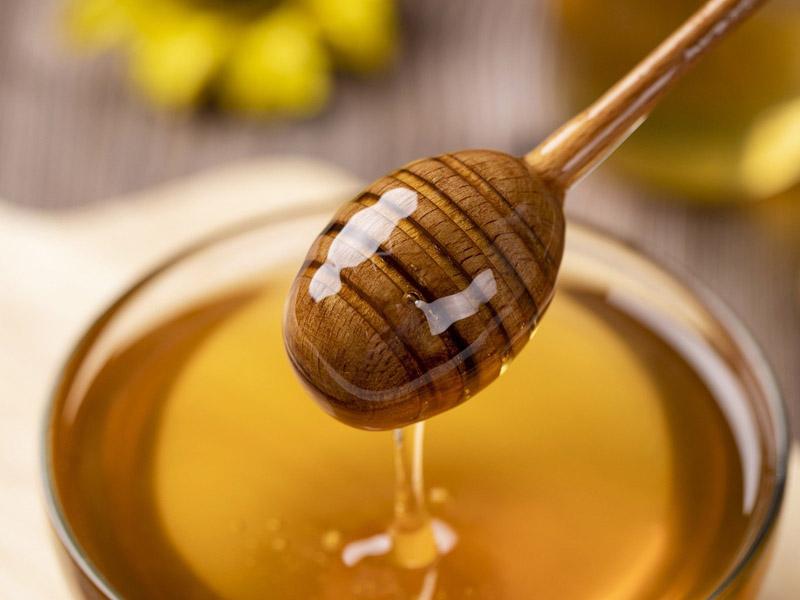 Honiglöffel mit Honig über Honigglas