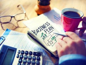Buch mit Businessplan, Kaffeetasse und Taschenrechner auf Tisch